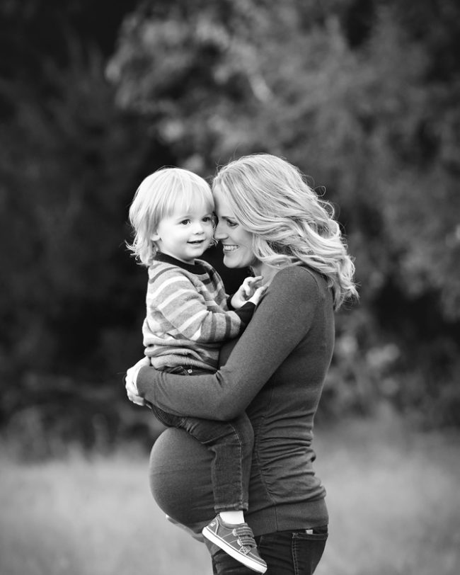 mom and son cuddling in outdoor pregnancy photo