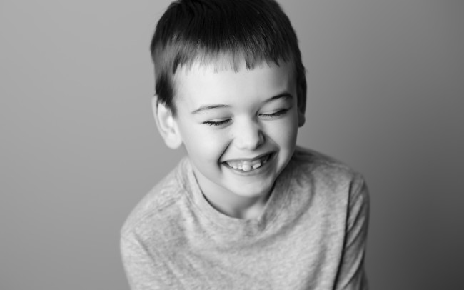 black and white headshot of boy giggling