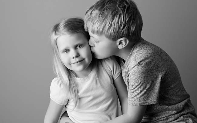 brother kissing sister cheek black and white