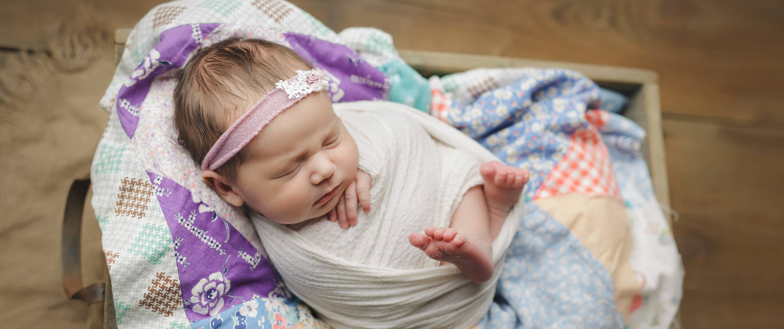 newborn girl wrapped with quilt lincoln nebraska photographer